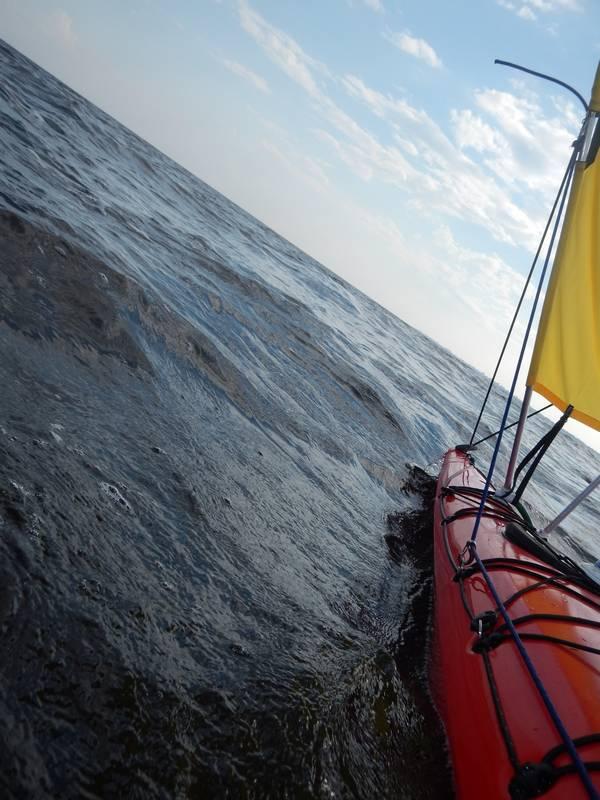 Пару слов о V-образном парусе на каяке. Неважно, покупном или самодельном.  1. Он предназначен для попутных направлений ветра. Для острого курса необходимо увеличить боковое сопротивление судна. Возможно, со скегом получится. 2. Не стоит гнаться за увеличением площади паруса. Если он маленький и не тянет при слабом ветре - это не страшно. Размер больший, чем позволяет лодка может легко ее перевернуть. Тем более столь узкий корпус как у каяка. При условии невозможности полноценного откренивания лодки, это весьма рискованно. У меня площадь ок.1.2кв.м и даже при порыве парус не затрагивает остойчивости Цунами-160. 3. Рулевая система Цунами-160 недостаточна для управления парусным вооружением. Во-первых, педали не позволяют чутко управлять лодкой. Во-вторых, площади рулевого пера не хватает даже на скорости. В качестве примера, при переоборудовании sit-on-top Hobie Adventure в тримаран Hobie Adventure Island площадь руля увеличивается примерно в 1.5 раза. 4. Для Цунами 160 существует лишь одна точка расположения паруса. Ближе к носу - некуда, ближе к кокпиту - будет мешать грести. На более длинных лодках - возможностей больше. В результате центр парусности смещен вперед, что также ухудшает управляемость лодки. 5. Парус на каяке - адреналиновое развлечение!!! И сильно упрощает жизнь.
