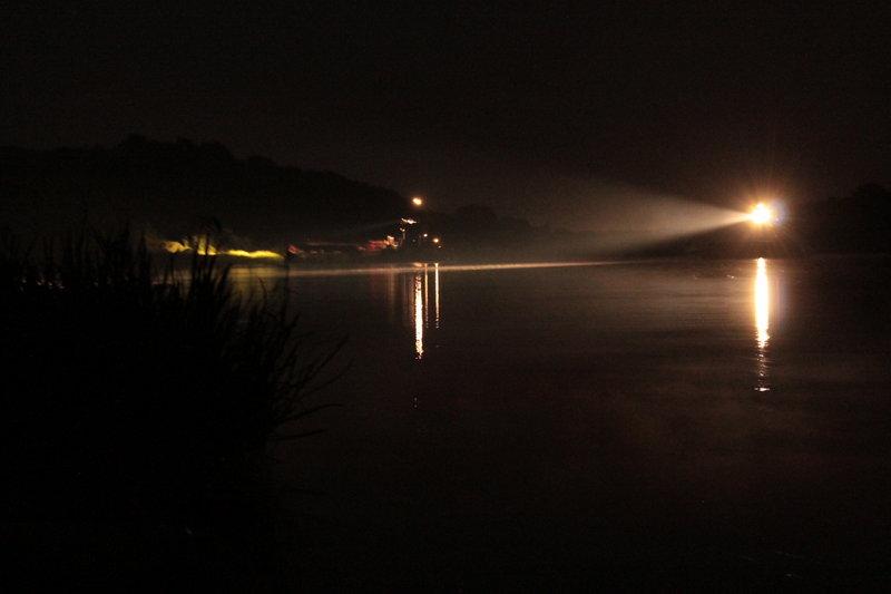 Баржа-труженица работала сегодня до самой поздней ночи, сверкая лучом прожектора по глади воды.