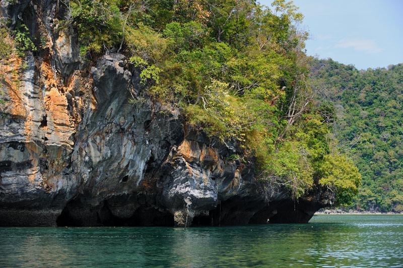 Акватория утыкана маленькими островами с живописными цветными скалами и бурной растительностью.