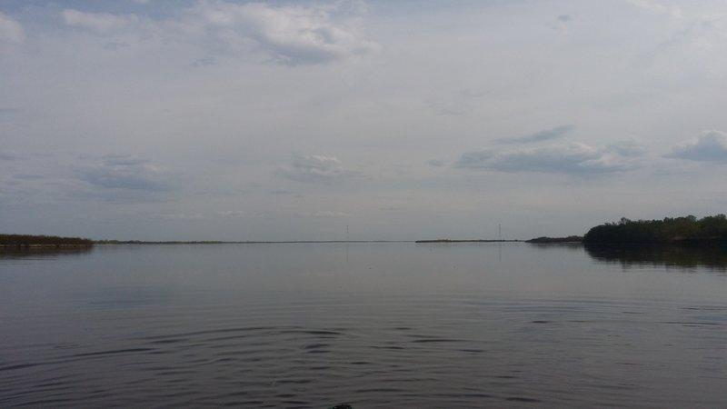 Прошли наконец длинный остров, видим реку во всей красе. Вода спокойная, тихая, как на озере. Вдали виднеются опоры ЛЭП, время 16:15.