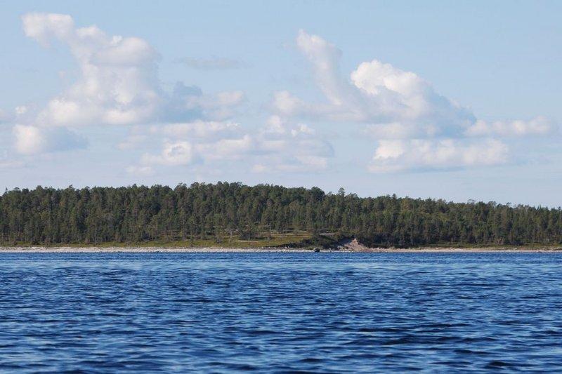 После мыса Кортнев прохожу небольшой залив, в вершине которого находится морской порог Купчиный, который ведёт в губу Бабье море. Ну а я шпарю мимо. Ориентир у меня всегда один и тот же: самый дальний мыс. Сейчас в этой роли выступает мыс Титов. От Кортнева до него 7 км. Когда оставалось 3 км, то стал различать какую-то вышку.