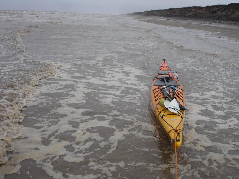 Вода оказывается не такой холодной и я в неопреновых тапочках вполне  могу брести по щиколотку в воде с голыми ногами. Берег пологий и  песчаный, лишь на мысах и в некоторых местах возникают выбросы камней и  мне приходится уходить поглубже, чтобы пройти эти участки. Скорость  буксировки 3-4 км/ч, при этом я устаю не очень сильно и не испытываю  никаких переживаний. Во время буксировки все время замечаю высоту  прилива и посматриваю вперед - берег обрывистый, и если начнет  прижимать, лодку будет не затащить и придется выходить в море, а на  приливе прибой заметно сильнее. Примерно через 1.5 часа, пройдя так 4.5  км, я замечаю на берегу трапик, и чуть дальше лодку в море на привязи -  значит тут есть люди. Решаю сделать остановку, тем более что дальше  начинается большой мыс, который уже подперло водой и пройти его берегом я  уже не смогу. Затащил лодку на берег, и пошел поискать людей. Здесь небольшой ручей и  изба стоит на нем. В избе встретил Татьяну и Александра из Каменки. Они  рассказали мне, что начался шторм, и его обещают на 4 дня. Начался он  вчера, соответственно, сегодня и еще пару дней мне лучше стоять на  берегу. Шторма здесь в это время редкость, а такой продолжительный - тем  более. Но вот, мне не повезло. Оставаться мне здесь неудобно, поэтому я  жду смены воды, чтобы продолжить путь. Сами они выехали собирать  морошку, но ягоды в этом году нет, а тут еще и  штормом прижало. Еды, конечно, взято надолго, а вот курева осталось на  3-4 дня - проблема! Меня угощают обедом, пьем чай, общаемся - в основном  Александр рассказывает мне о местных особенностях. Свою лодку они  вдвоем вытащить на крутой берег не могут, поэтому сняли с нее все и  оставили в море на якорях, там где меньше камней и ее не будет сильно  бить. В самый прилив лодку все равно постепенно заливало водой, выбило  стекло, но она еще держалась на плаву. Александр ждал отлива, чтобы  пройти к лодке и откачать воду.  Дождавшись, когда вода немного убыла, я собрался с духом и вышел в море.  П