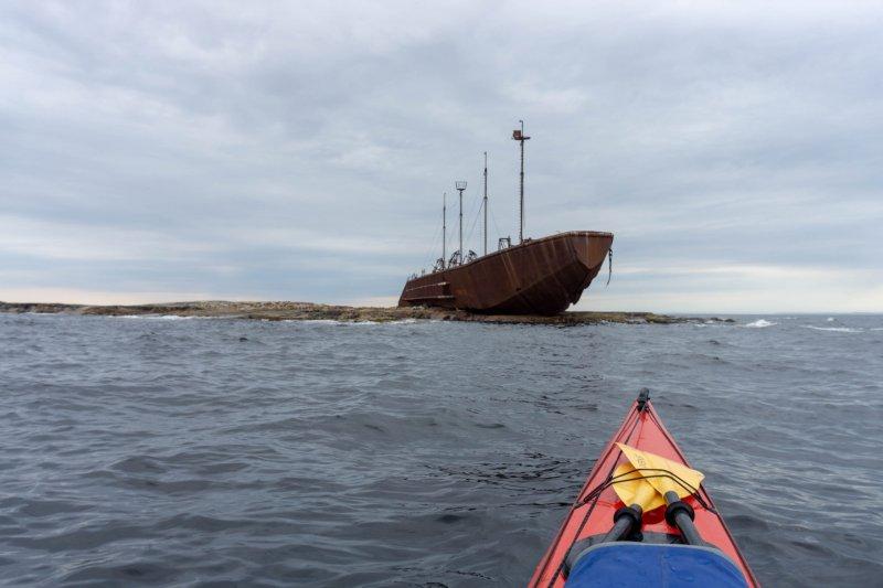 Я обогнул Кемлудский, Асафий и другие острова и пройдя мыс Наблюдателей увидел затопленный корабль. Судя по оторванной корме, судно выбросило на скалы, а задница вместе с рубкой и двигателем ушла под воду. Эпичное зрелище! ) Конечно я не удержался от соблазна посетить судно. Входного билета не было и залезать пришлось с затопленной кормы прямо из воды закидывая пятку выше головы чтобы выкатить свое тело на палубу. Было несколько альтернативных путей, например через дыру в днище попасть внутрь грузового трюма и там по лестнице забраться наверх. Но элементы лестницы были на столько ржавые и некоторые уже успели отвалиться сами по себе, пошевелив одну из них она упс, упала от стены. Решил не рисковать. Остаться на мелком острове с кораблем в 7 км от берега не хотелось. Палуба уже успела обрасти мхом и цветами, из оборудования ничего не сохранилось, а внутри выброшенной на берег части судна только грузовые отсеки. Так что забравшись на нос и посмотрев в даль на усиливающийся ветер, я подумал: надо бы валить отсюда поскорее, пока не разгулялась волна. Оставив погибшее судно я погреб через залив к острову Сидоров, и там найдя еще более мелкие островки встал на стоянку. Меня утешала мысль, что на таком мелком острове точно нет медведей, и я смогу нормально выспаться )